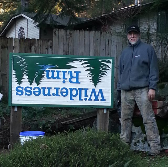 Doug Greathouse standing next to the Wilderness Rim entrance sign, which is mounted upside down.